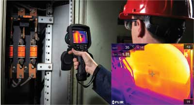 An inspector using their FLIR EXX thermal imager inside an electrical panel.